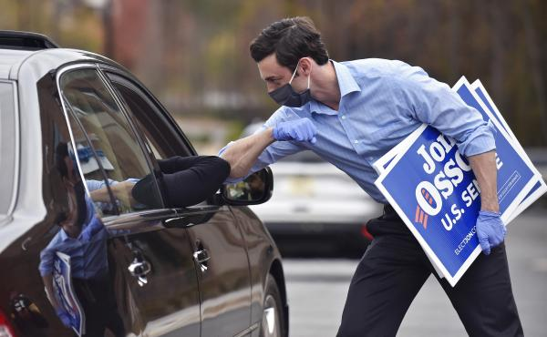 Jon Ossoff, a Georgia Democratic candidate for U.S. Senate, greets a supporter with an elbow bump at a drive-through event to pick up yard signs last month in Alpharetta, Ga. Ossoff is in a runoff with Republican David Perdue, the incumbent, for the U.S.