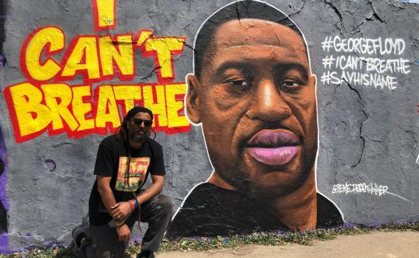 """Graffiti artist Eme Freethinker kneels in front of his portrait of George Floyd, which he painted on one of the last remaining sections of the Berlin Wall. """"I remember when I came in [to paint it], some guy told me, 'You have to do it with the police over"""