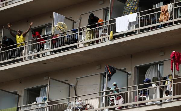Migrants wave from the their balconies in Kranidi, southern Greece, on Tuesday. Authorities confirmed a high number of COVID-19 infections at the site.