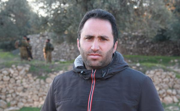 Palestinian activist Issa Amro advocates nonviolence in the West Bank city of Hebron. He recently talked a teenage girl out of an attack, but acknowledges it can be difficult to persuade young Palestinians to his position. In the background, Israeli soldi