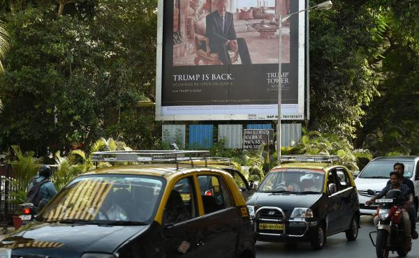 A billboard for the Trump Tower Mumbai luxury residential apartment complex is seen next to a busy road in Mumbai in June.