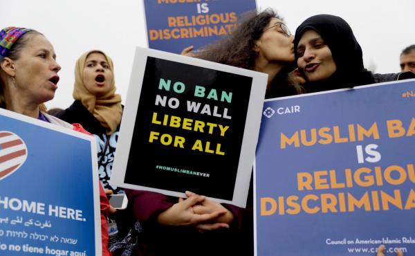 Deeba Jafri gives Hena Zuberi a kiss as they protest in front of Supreme Court on Wednesday as the court heard arguments over the Trump Administration's travel ban.