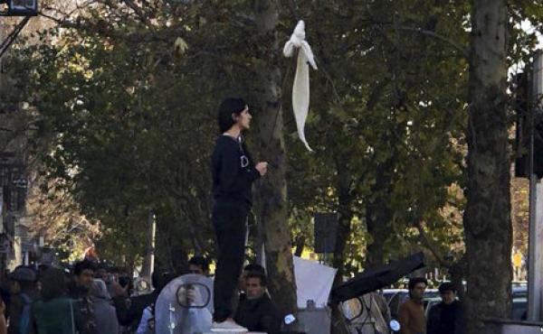 Vida Movahed stands on a telecommunications box, holding a headscarf on a stick in protest against Iran's mandatory hijab rules, in Tehran in December. Since then, Iranians have staged various protests for women's rights.