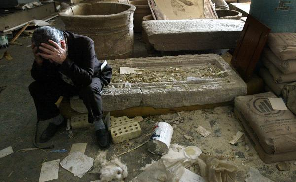 Iraqi National Museum Deputy Director Musin Hassan holds his head in his hands as he sits amid destroyed artifacts in the Baghdad museum in 2003.
