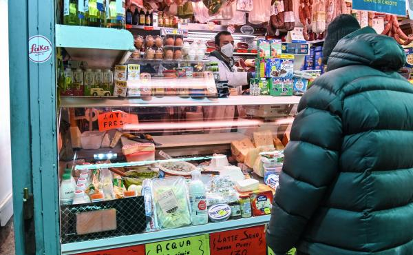 A vendor wearing protective masks and gloves serves a customer at a market in Rome on April 16.