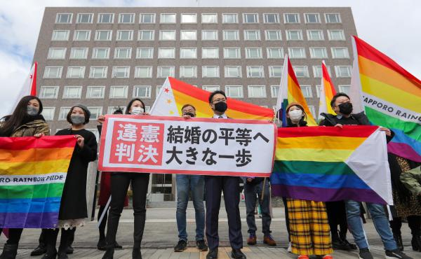 """Supporters celebrate the district court's ruling on Japan's same-sex marriage ban with a flag reading """"unconstitutional decision"""" in Sapporo, Hokkaido prefecture, on Wednesday."""