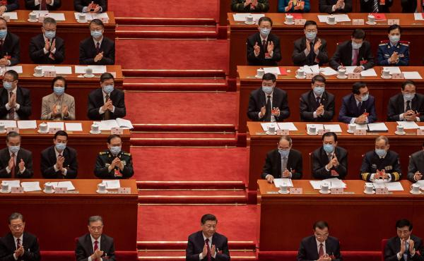China's President Xi Jinping (C) applauds with other leaders and delegates after they voted on changes to Hong Kong's election system during the closing session of the National People's Congress at the Great Hall of the People in Beijing on March 11, 2021