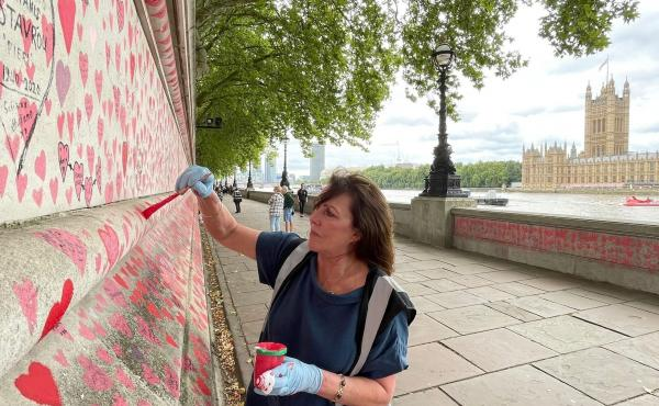 Fran Hall paints hearts on a memorial in London dedicated to people who have died from COVID-19. She and other activists are pushing for the British government to investigate its handling of the pandemic.