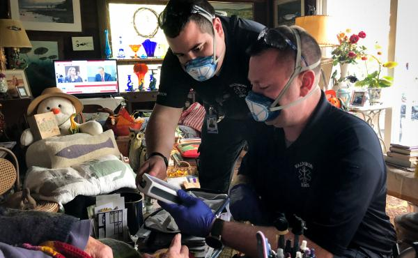 In between answering 911 calls, Jerrad Dinsmore (left) and Kevin LeCaptain perform a wellness check at the home of a woman in her nineties. The ambulance team in the small town of Waldoboro, Maine was already short-staffed. Then a team member quit recentl