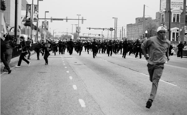 """A man runs from a line of charging police in riot gear in Baltimore. The photo, taken by Devin Allen, is featured in the National Museum of African American History and Culture's newest exhibit, """"More Than A Picture."""""""