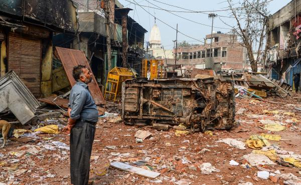 A resident surveys the damage following clashes in New Delhi on Wednesday. At least 20 people have died in three days of violence.