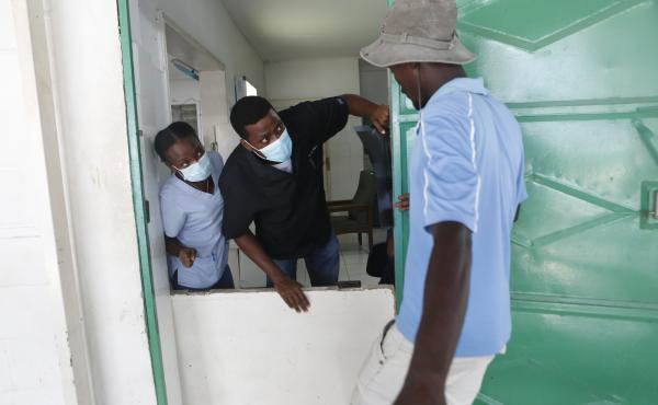 Dr. Antoine Titus talks to a walk-up patient at Immaculée Conception Hospital in Les Cayes, Haiti, where he was made chief physician the day of the 7.2 magnitude earthquake.
