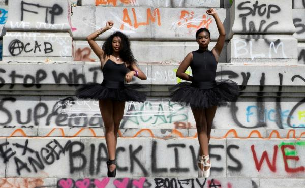 Ballerinas Kennedy George, 14, and Ava Holloway, 14, pose in front of a monument of Confederate general Robert E. Lee after Virginia Governor Ralph Northam ordered its removal after widespread civil unrest following the death in Minneapolis police custody