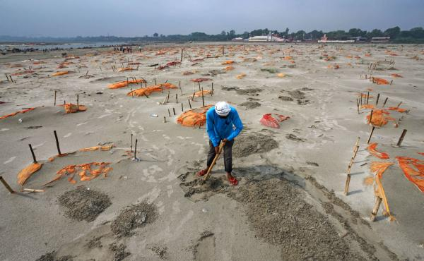 Rains have washed away the top layer of sand of shallow graves at a cremation ground on the banks of the Ganges River in Shringverpur, northwest of Allahabad, Uttar Pradesh, India. Coronavirus testing is limited in parts of rural India, but some of the pe