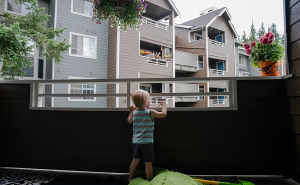 Grigory Vodolazov's 3-year-old son peers into his family's apartment complex from their unit in Bellevue, Wash. The Vodolazov family is part of Creating Moves to Opportunity, a housing voucher experiment that uses incentives and counseling to encourage lo