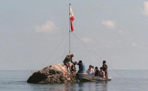 In this file photo, Philippine navy personnel and congressmen land at a rock that is part of Scarborough Shoal bearing the Philippine flag that was earlier planted by Filipino fishermen.