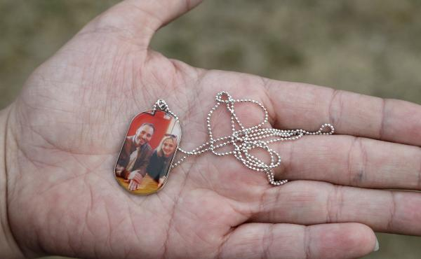 Aya Al-Umari, whose brother Hussein Al-Umari was killed in the Al Noor mosque shooting, holds a pendant with a photo of herself and Hussein during an interview at her home in Christchurch, New Zealand.