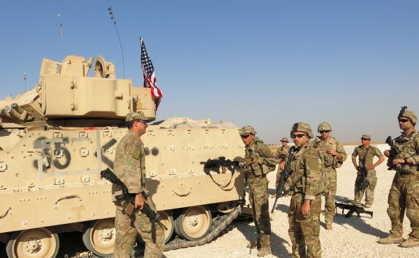 A new U.S. brigade combat team arrives in front of a Bradley Fighting Vehicle at a base in Syria's Hasakah province.