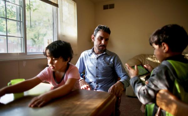 Omar Al-Awad sits with his daughter Taiba (left) and son Abdul-Jabar in their Toledo apartment in 2015.