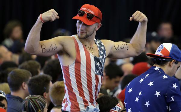 """A Trump supporter flexes his muscles with the words """"Build The Wall"""" written on his biceps, as Trump speaks at a campaign rally last year."""