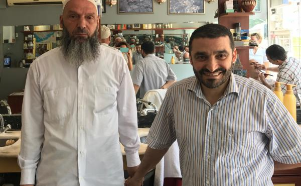 Suat Keceli, left, a retired stockroom worker, and his barber Yasar Ayhan pose in Ayhan's barber shop in Kasimpasa, the Istanbul neighborhood where President Recep Tayyip Erdoğan grew up. Keceli is a conservative Muslim who kept his daughter out of schoo