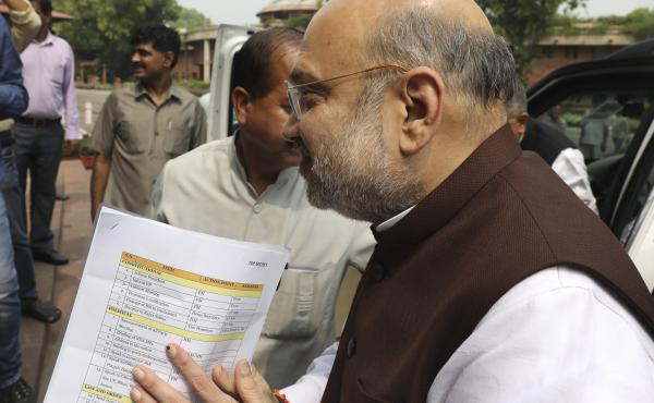 Indian Home Minister Amit Shah arrives at the Parliament on Monday carrying a copy of a confidential document that lists the procedure for revoking Kashmir's special status in New Delhi.