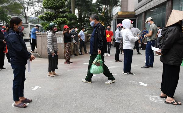 People wearing face masks wait for free food being given away at a Happy Mart store in Hanoi on Thursday.