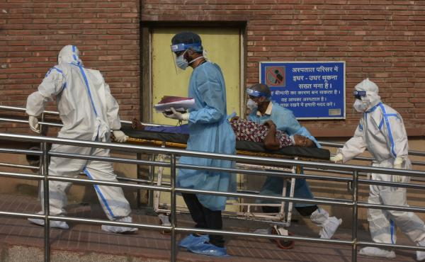 Medical professionals escort a patient into the the COVID-19 ward at Lok Nayak Jai Prakash Hospital in New Delhi on June 15.