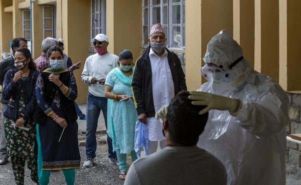 A health officer in a protective suit collects a swab sample to be tested for the coronavirus on Thursday in Dharmsala, India. India's confirmed coronavirus caseload surpassed 8 million on Thursday.