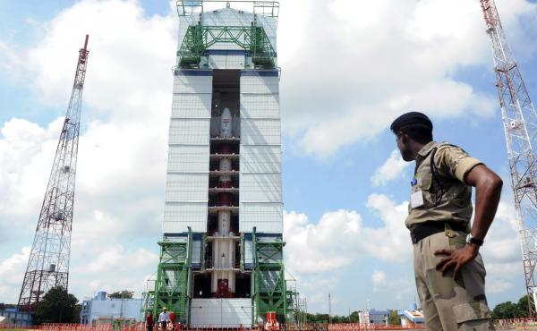 A member of the Indian security force keeps watch over a launch vehicle carrying the Mars Orbiter probe at the Indian Space Research Organization facility, in Sriharikota, in 2013.