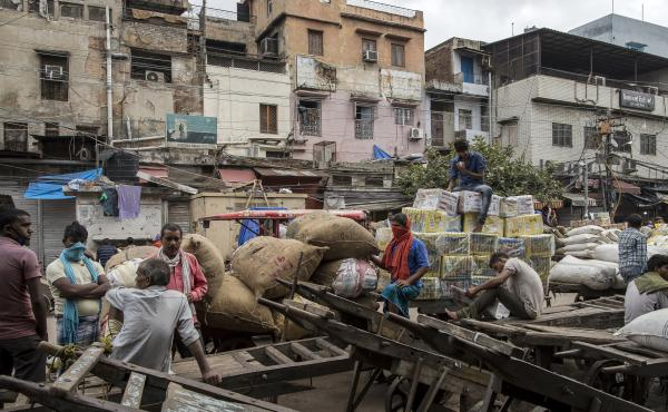 Workers and day laborers gather outside shuttered stores Monday in New Delhi. Once the world's fastest-growing major economy, India posted its steepest decline in gross domestic product in 24 years.