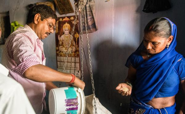 Ashok Kumar distributes government food rations to customer Leela Devi at his shop near Ramgarh, in India's Jharkhand state.