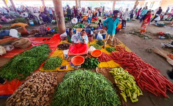 Farmers, traders and customers weave through waist-high heaps of chili peppers, piles of ginger and mounds of carrots at a government-run wholesale market in western India.