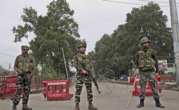 Indian paramilitary soldiers stand guard near a temporary check point on the road leading toward an Independence Day parade venue during lockdown in Srinagar, in Indian-controlled Kashmir, on Thursday. Indian Prime Minister Narendra Modi says that strippi