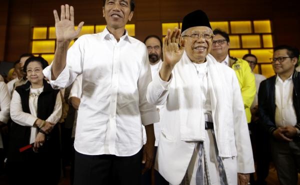 Indonesian President Joko Widodo (left) and his running mate, Ma'ruf Amin, wave to journalists after a news conference in Jakarta, Indonesia, on Wednesday.
