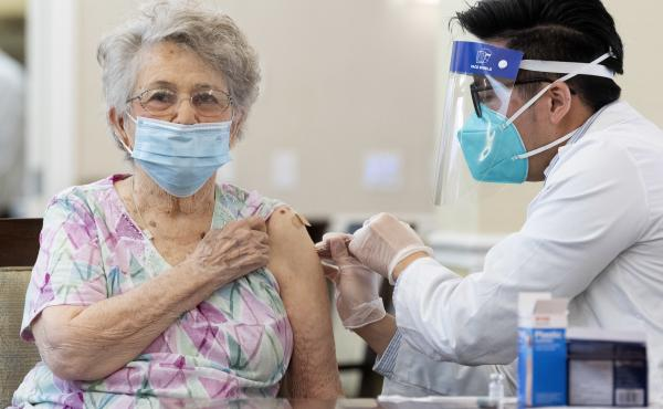 A CVS pharmacist gives the Pfizer/BioNTech COVID-19 vaccine to a resident at the Emerald Court senior living community in Anaheim, Calif., in January. Federal health officials have revised advice on nursing home visitations for the first time since Septem