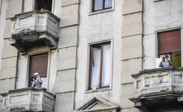 People lean out of their homes' balconies to play and sing during a flash mob in Milan, Italy, Friday, March 13, 2020. Italians have not been able to leave their homes since March 9, when the government locked the country down to combat the spread of coro