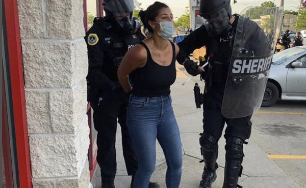 Police officers are shown arresting Des Moines Register reporter Andrea Sahouri after a Black Lives Matter protest she was covering on May 31, 2020, in Des Moines, Iowa. Sahouri went on trial Monday on charges of failing to disperse and interfering with o