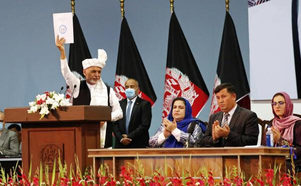 Afghan President Ashraf Ghani holds up a resolution on the last day of a traditional council known as a Loya Jirga, in Kabul, Afghanistan, Aug. 9. The council concluded with hundreds of delegates agreeing to free 400 Taliban members, paving the way for an