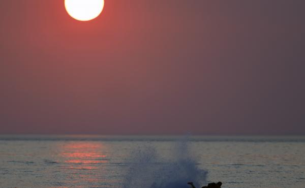 Western wildfires create a hazy sky as a person surfs on the water in Indiana Dunes State Park on Tuesday.