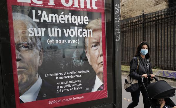 """The French weekly Le Point displays a photo of President Trump and Democratic presidential candidate Joe Biden under a headline reading """"America on a volcano (and us too)"""" in Paris, on Wednesday."""