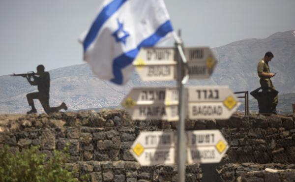 An Israeli soldier is seen next to signs pointing out distances to different cities on Mount Bental next to the Syrian border on Thursday.