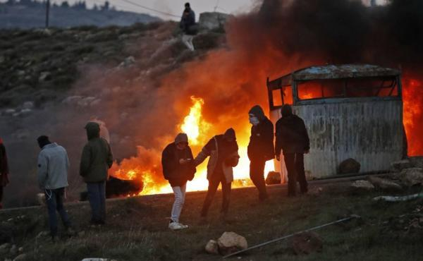 Jewish settlers set tires ablaze at the Amona outpost, northeast of Ramallah, on Wednesday.