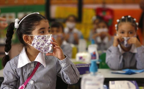 Palestinian elementary school students wearing protective face masks take their seats in their classroom amid the coronavirus pandemic on the first day of class in September at a United Nations-run school in the West Bank city of Ramallah.