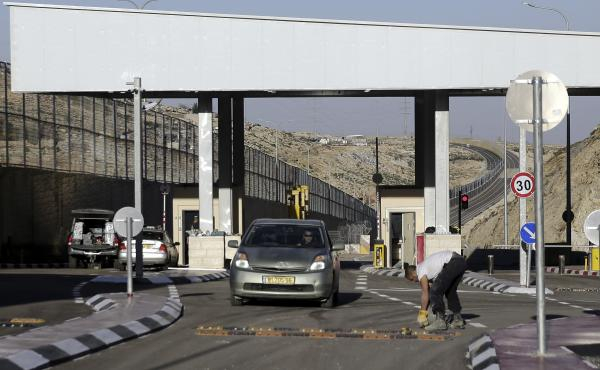 """A checkpoint is seen on a West Bank highway near Jerusalem  which critics have branded an """"apartheid highway."""" The highway features a large concrete wall segregating Israeli and Palestinian traffic."""