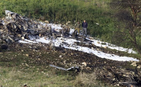 Israeli security stands around the wreckage of an F-16 that crashed in northern Israel on Saturday. The Israeli military shot down an Iranian drone it said infiltrated the country before launching attacks on at least a dozen Iranian and Syrian targets ins