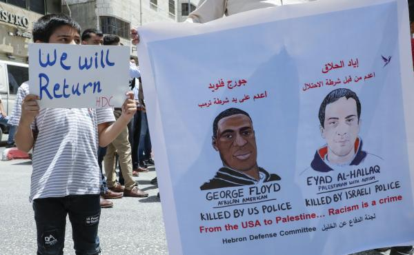 Palestinians lift banners protesting the killing of Eyad Hallaq, a Palestinian man with autism shot dead by Israeli police, and the case of George Floyd, an unarmed black man killed by policeman in the U.S., during a rally by supporters of the Fatah movem