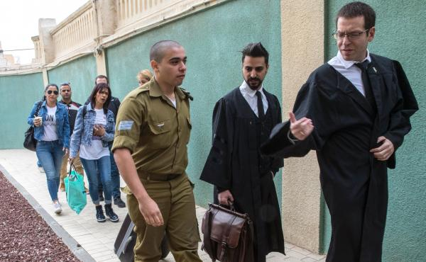 Israeli soldier Elor Azaria, who was caught on video shooting a wounded Palestinian assailant in the head as he lay on the ground, speaks with his lawyers upon his arrival for a hearing at a military appeals court in Tel Aviv on Nov. 23, 2016. Azaria has