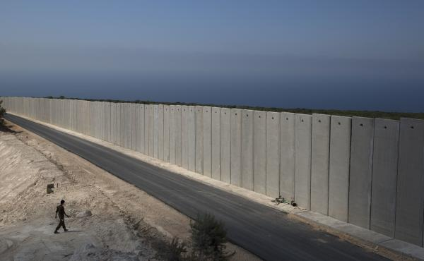 "An Israeli soldier, seen in September, stands near a wall along the Israel-Lebanon border near the Israeli region of Rosh Haniqra. The Israeli military says it has launched an operation intended to ""expose and thwart"" tunnels built on the border by the He"