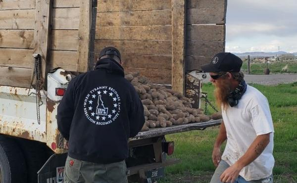 Members of the Real Idaho Three Percenters unload potatoes this week as part of a volunteer effort to give away crops that were unsold because of the coronavirus pandemic. Their activities raise questions about the role of militias in the pandemic respons